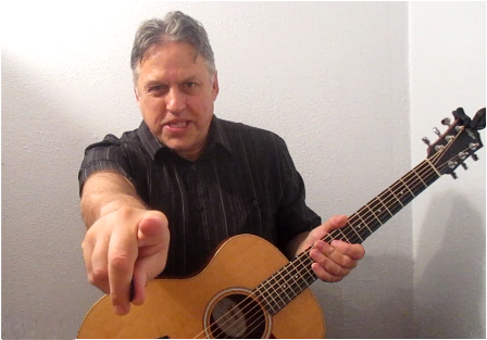 Guitar Lessons, Free Sample Video Links, Tablature, Tips and Updates  Dennis Hartman, snaring, holding the guitar and pointing at the reader