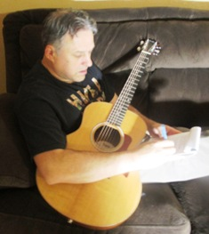 Free Original Songs - Dennis Hartman with guitar holding pen and paper and writing a song